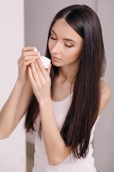 コンセプトスキンケア。清潔で新鮮な顔に化粧用クリームを持つ若い健康な女性。美しさと健康。顔の美容治療のコンセプト。画像。