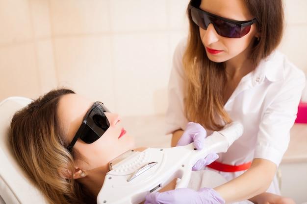 ボディケア。若い女性の顔にレーザー脱毛治療を与える美容師のクローズアップ