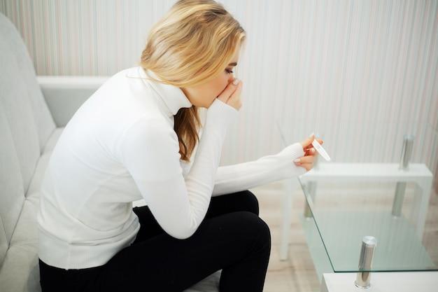 Взволнованная грустная женщина, смотрящая на тест на беременность после результата