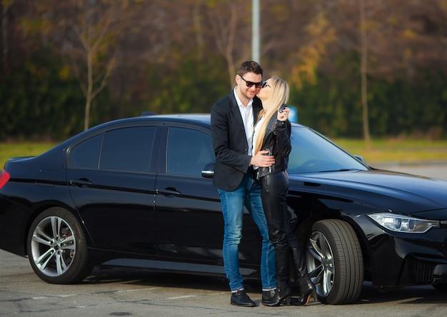 Счастливая пара покупает новый современный черный автомобиль