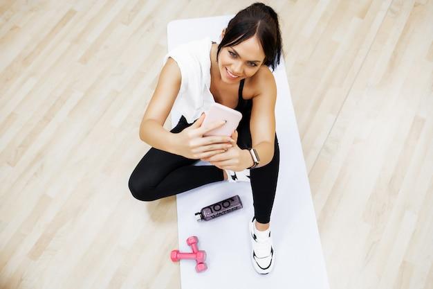 健康的な生活様式。ジムで運動をしているフィットネス女性