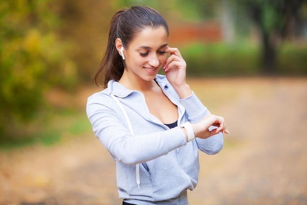 音楽を聴くランナー。フィットネス、スポーツ、健康的なライフスタイル-イヤホンで笑顔のランナー
