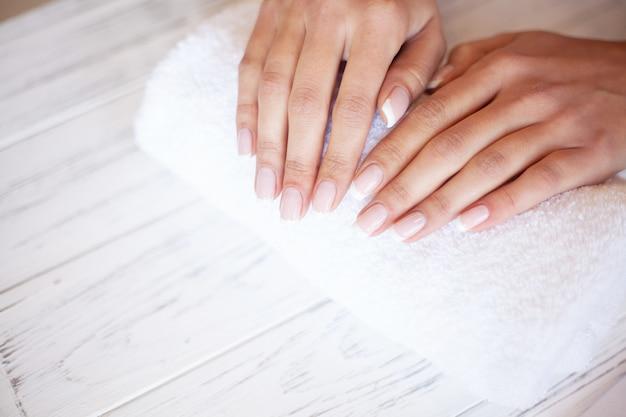 女性の手のケア。ビューティーサロンでスパマニキュアを持つ美しい女性の手のクローズアップ。美容師ファイリングクライアントネイルファイルと健康的な自然な爪。ネイルトリートメント