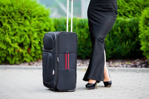 Подрезанное изображение путешественник турист женщина скрещенные ноги летом с чемоданом на дороге в городе открытый.