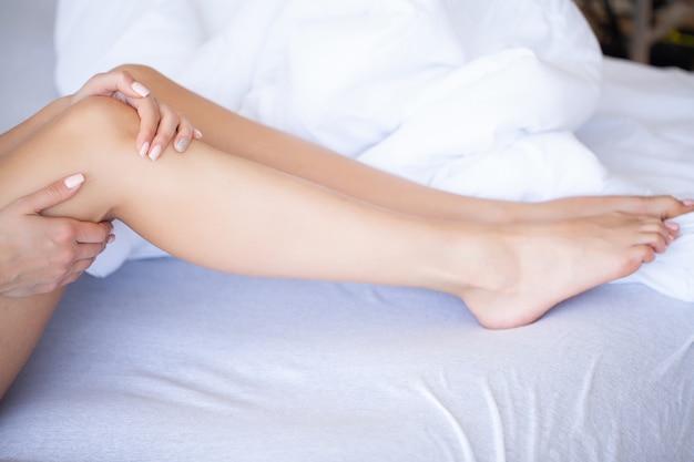 女性の足が荷物で育った、自宅で若い女性がベッドに横たわっています。白い寝室。