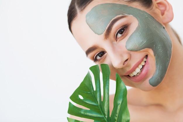 フェイスマスク。顔にマスクを適用する美しい笑顔の女性