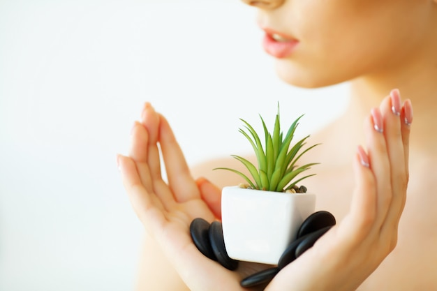 スキンケア。緑のアロエベラの植物を保持している明確な肌を持つ女性。ビューティートリートメント。美容。ビューティースパサロン