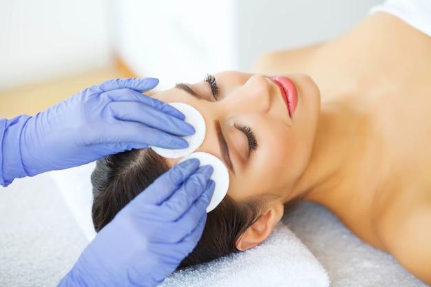 Красота. молодая девушка в салоне красоты. косметолог очищает кожу лица с помощью ватных дисков. лежа на массажных столах. чистая и свежая кожа. забота о коже.