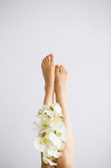 美しい柔らかい肌。完璧な毛のない滑らかで絹のような肌を持つ長い女性の足のクローズアップ。脱毛、美容ボディケア