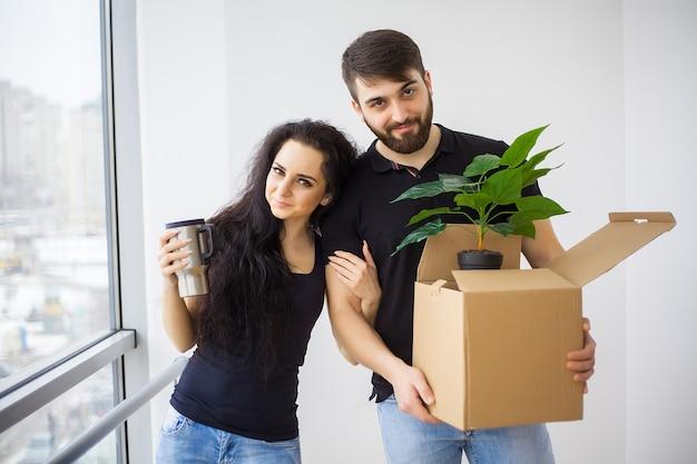 カメラ目線を抱いて新しい家にキーを示すカップル