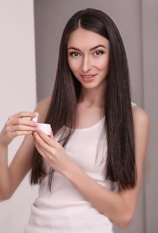 清潔でさわやかな肌を持つ美しい若い女性は、顔に触れます。フェイシャルトリートメント、美容、美容、スパ