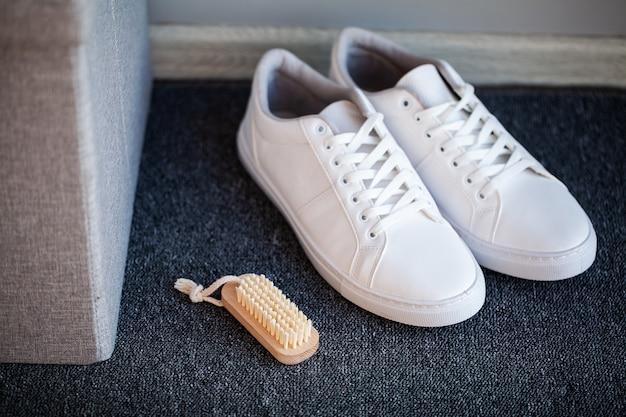 家の床に新しいスタイリッシュな白いスニーカーのペア