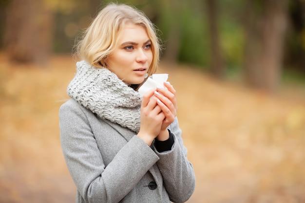 公園で彼女の鼻を吹く若い女性。