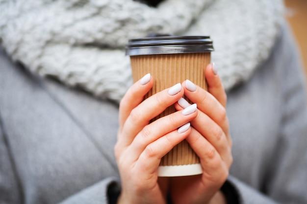 行くコーヒー。秋の公園でコーヒーを持つ若い女性