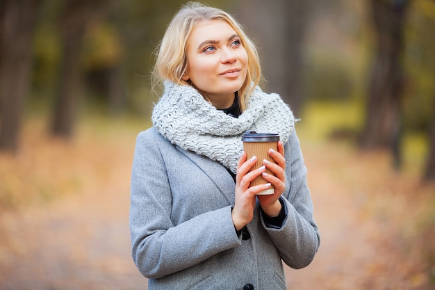 Кофе с собой. молодая женщина с кофе в осеннем парке