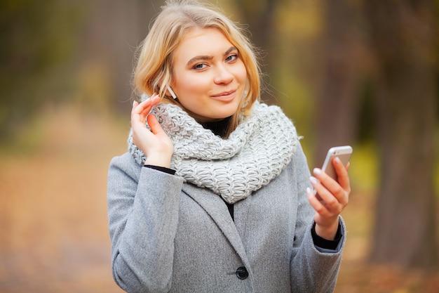 Молодая красота женщина прослушивания музыки в осеннем парке