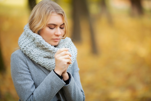 風邪やインフルエンザ。秋の公園を歩いてグレーのコートを着た若い女性と凍った手を温める