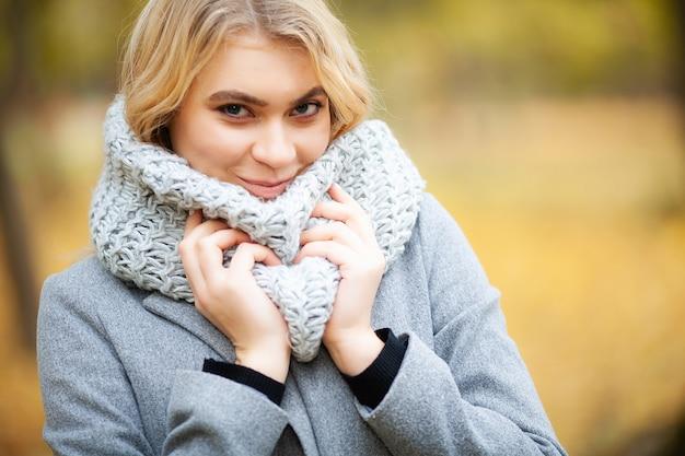 秋の公園を歩いてグレーのコートを着た若い女性