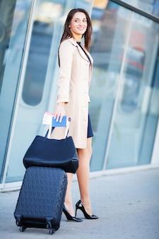 Улыбающаяся женщина с чемоданом и паспортом возле аэропорта