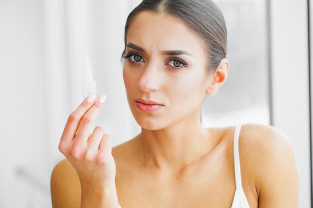 若い女の子は、手で目薬を保持します。