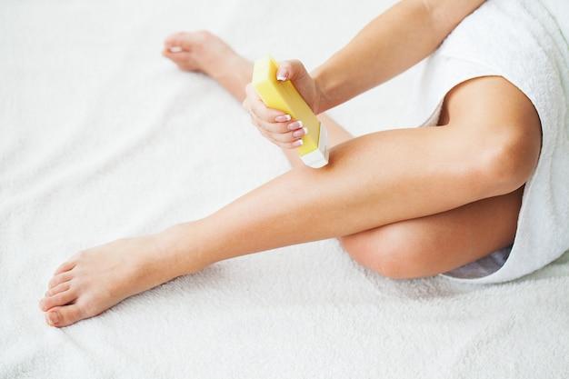 女性は浴室で脱毛のためにワックスを塗る