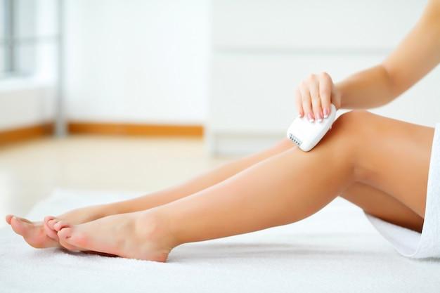 スキンケア。バスルームで彼女の足を剃る女性