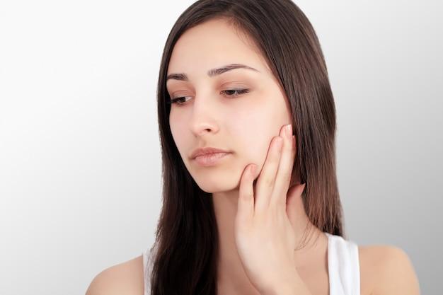 歯の痛みを感じる女性。