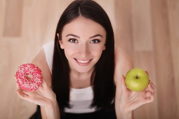 Стройная женщина держит в руке розовый пончик и зеленое яблоко