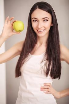 スリムな女性は手に緑のリンゴを保持します。
