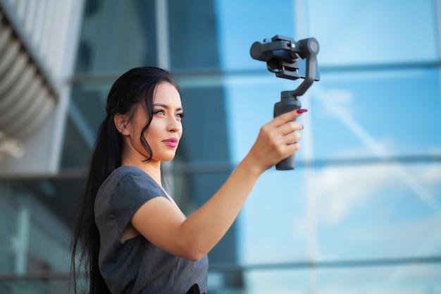 ブロガーの少女は、電子スタビライザーでの旅行に関するビデオを撮影します。