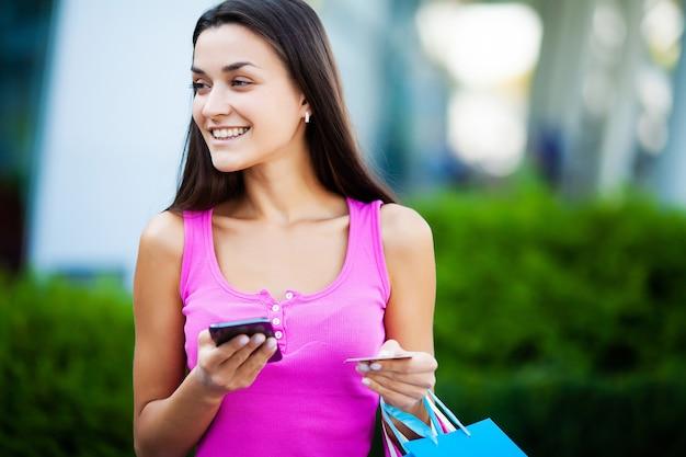 Счастливая женщина возле торгового центра с подарочными пакетами
