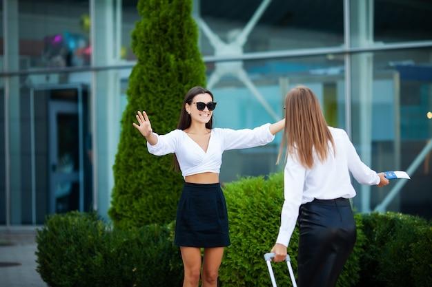 Молодые девушки встречаются в аэропорту