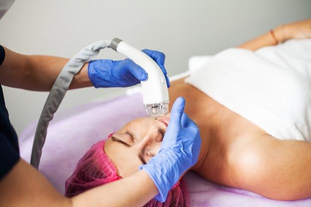 Женщина получает массаж в клинике красоты