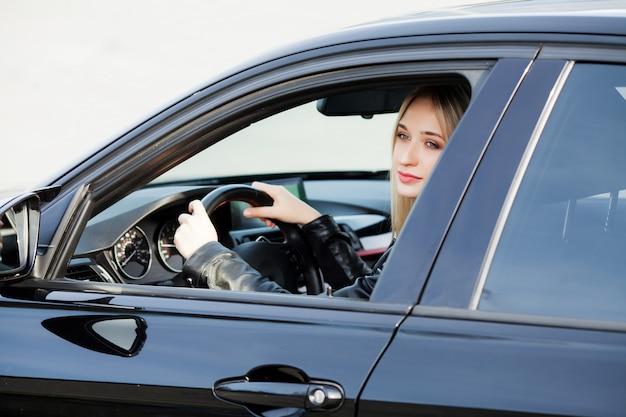 幸せな女は、新しい近代的な車を買って楽しんでいます
