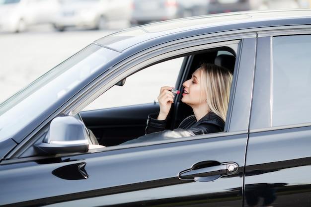 女性は彼女の新しい車の中に口紅を使用します