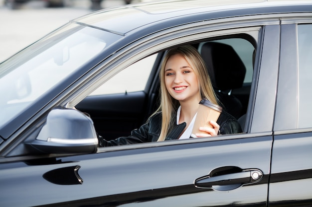 Счастливая женщина с удовольствием купила новый современный автомобиль