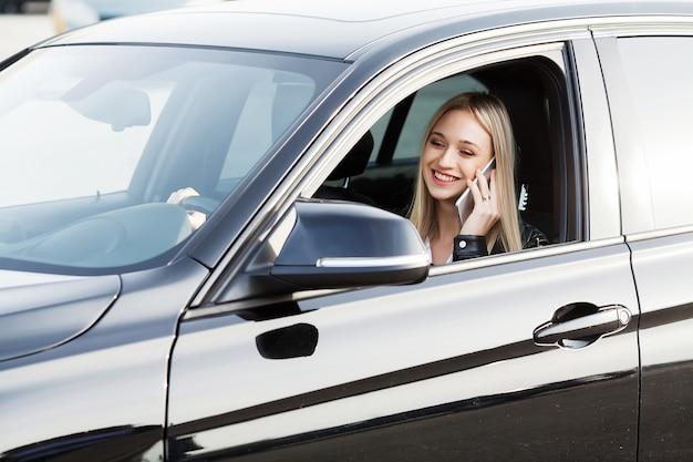 幸せな女は新しい近代的な車を買って楽しんで、友人に電話をかける