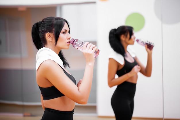 フィットネス女性は、ジムで水を飲む