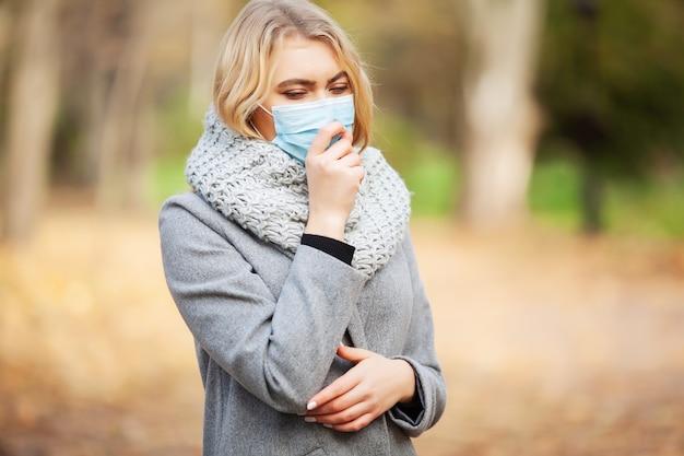 秋の森の医療フェイスマスクを持つ女性
