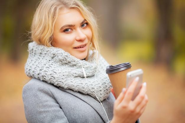 秋の公園でコーヒーを持つ若い女性