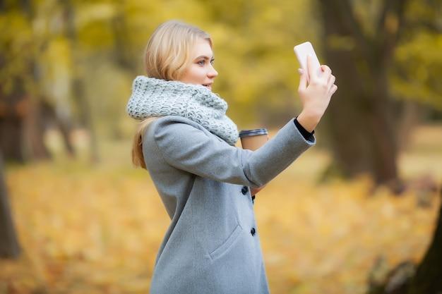 スマートフォンで写真を作る若い女性