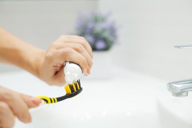 女性は明るい浴室で彼女の歯を磨く