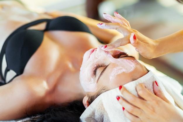 美容師は女性の顔に化粧品のマスクを塗ります