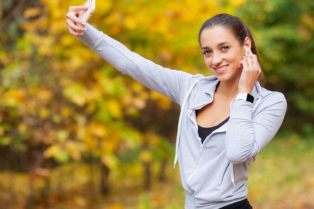 スマートフォンを見て、自分の写真を撮る長い茶色の髪を持つ若い女性