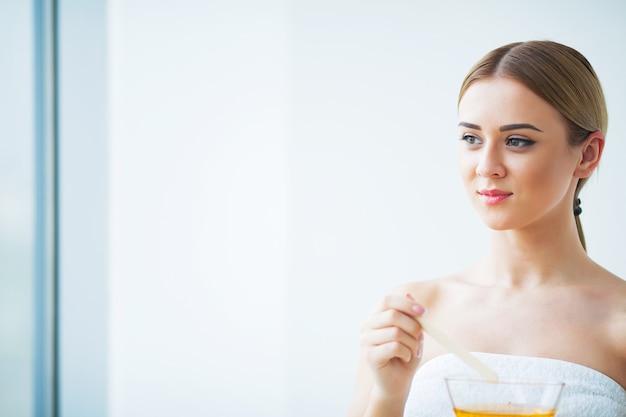 女性はオレンジ色のパラフィンワックスボウルを保持します。