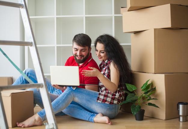 幸せな若いカップルが開梱し、新しい家に移動