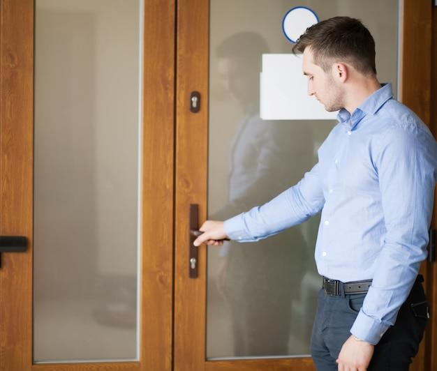 彼のオフィスのドアを開く企業マン