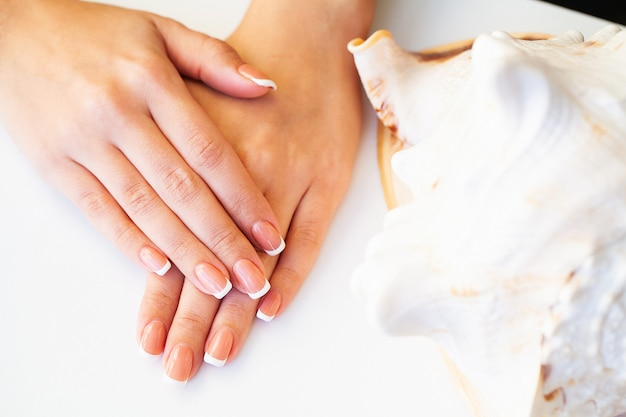 ビューティースタジオで、フランスのマニキュアと美しい女性の爪