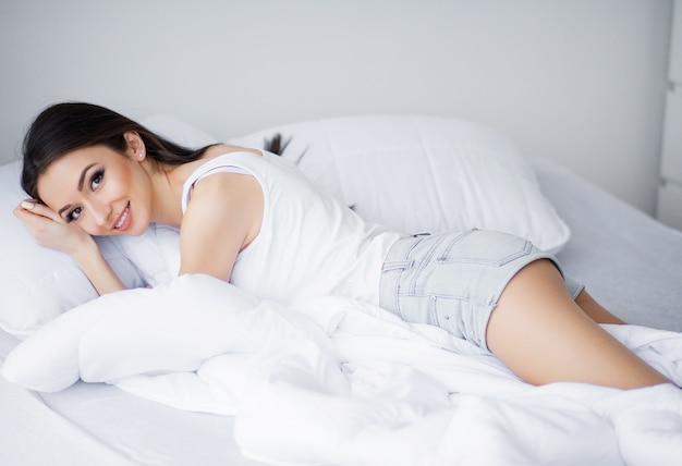 Счастливое утро, портрет улыбающегося довольно молодая брюнетка, расслабляющий в белой кровати