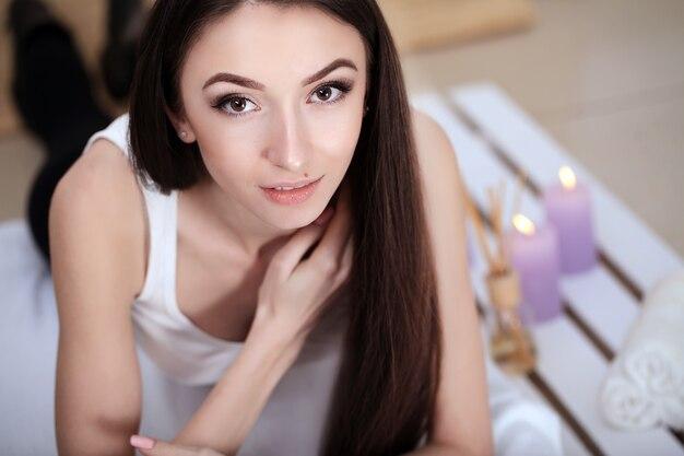 スパサロンでマッサージテーブルの上に横たわる美しい若い女性